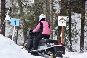 Lady on snowmobile entering trail
