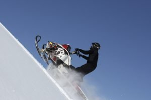 man on snowmobile climbing up hill